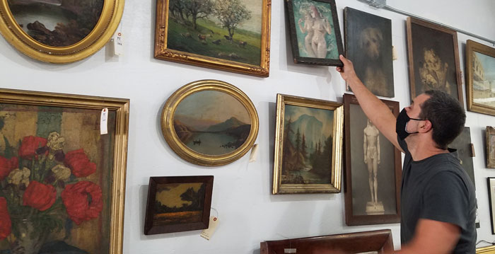 Co-owner of Public Sale auction house, Gabe Constantine, taking down a painting to show customer in showroom in Hudson, NY.